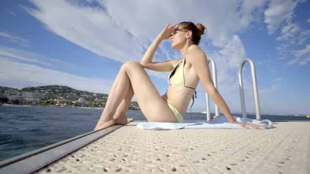 vídeos de stock, filmes e b-roll de pretty young adult female in bikini sunbathing - toalha de praia
