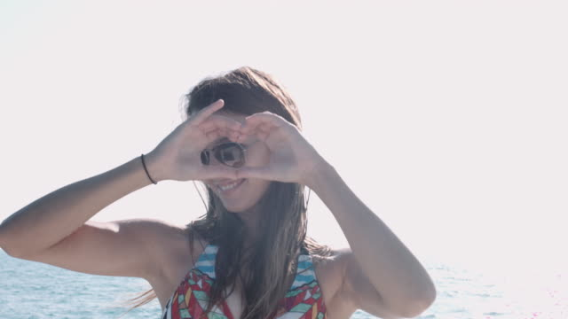 Pretty young adult woman making heart shape symbol with hands