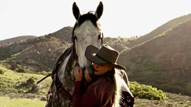 pretty young blond cowgirl leading her horse stops to scratch his nose - cowgirl stock videos & royalty-free footage