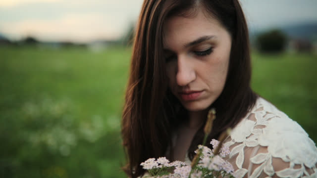 pretty young bride holding flower arrangement while standing in beautiful nature - flower arrangement stock videos and b-roll footage