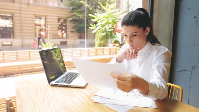 vidéos et rushes de jolie jeune femme d'affaires travaillant dans un café. - dossier document