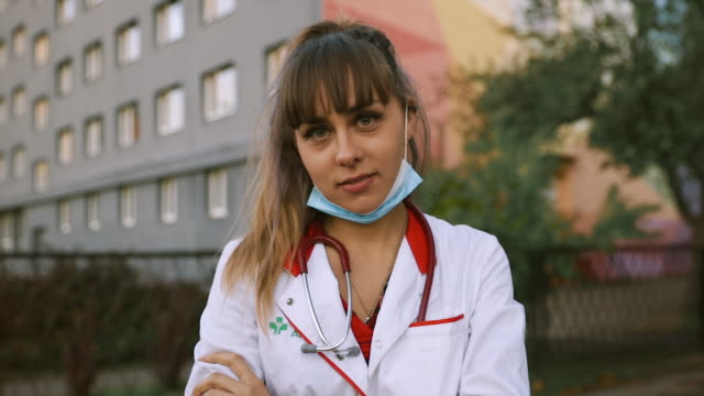 vídeos de stock, filmes e b-roll de pretty young female doctor in lowered medical mask with lgbt rainbow bracelet looks at you - estudante universitária