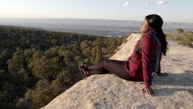 pretty young millennial african american woman sitting back on a cliffside enjoying a break watching the sunset during a hike in the mountains near fruita colorado - active lifestyle stock videos & royalty-free footage