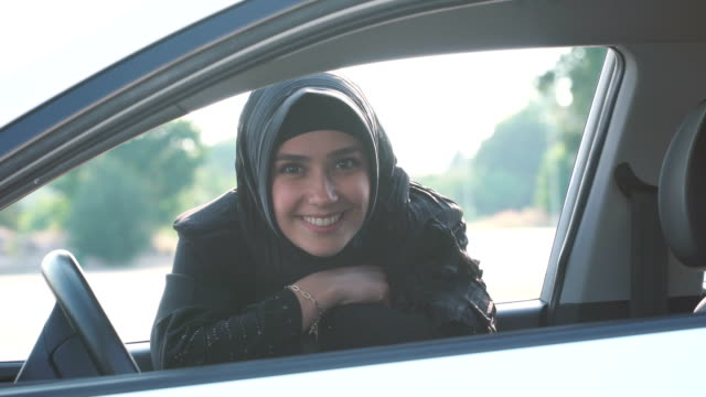 pretty young muslim woman smiling through at car window - test drive stock videos & royalty-free footage