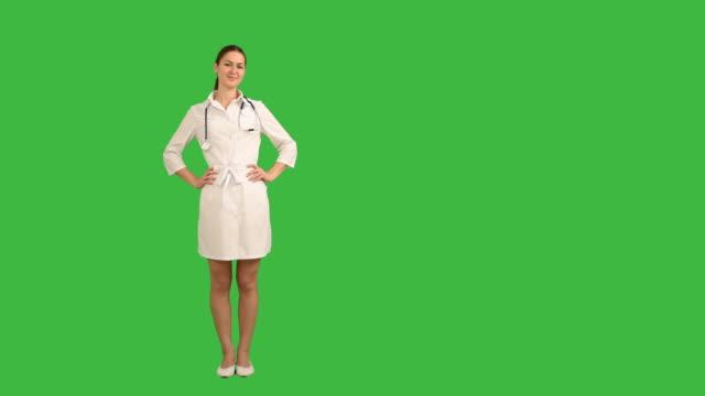 vidéos et rushes de jolie jeune infirmière est souriant et en regardant la caméra sur fond vert - doctoresse