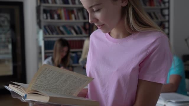 Hübsche junge Studentin in der Bibliothek, die ein Buch lächelnd liest