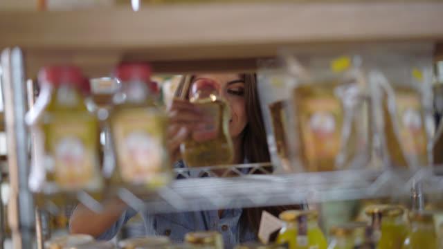 vídeos de stock, filmes e b-roll de muito jovem, escolhendo um produto shelve muito feliz e sorridente - escolher