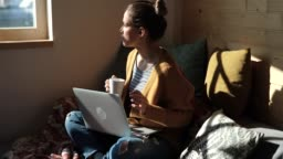 Pretty Young Woman Drinking Coffee And Working From Home in Cozy Sunny Atmosphere