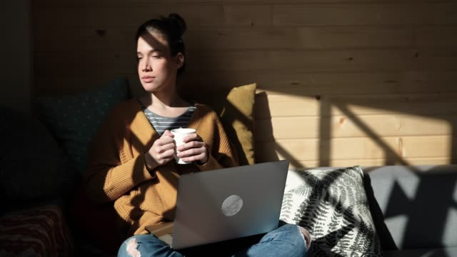 pretty young woman drinking coffee and working from home in cozy sunny atmosphere - comfortable stock videos & royalty-free footage