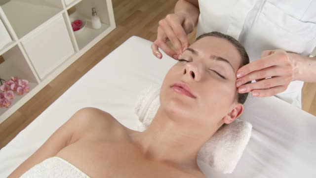 hd crane: pretty young woman enjoying facial massage - facial massage stock videos and b-roll footage