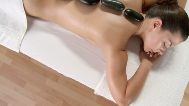 hd crane: pretty young woman enjoying lastone therapy - lastone therapy stock videos and b-roll footage