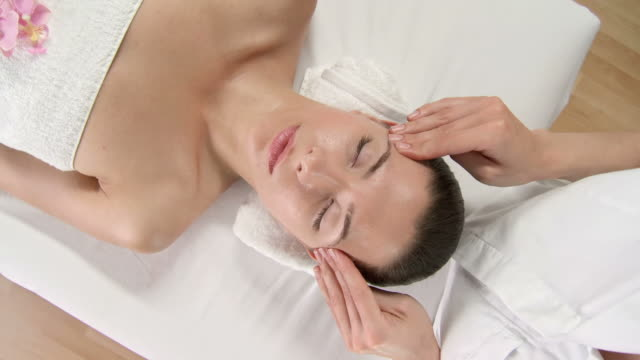hd crane: pretty young woman enjoying relaxing facial massage - facial massage stock videos and b-roll footage