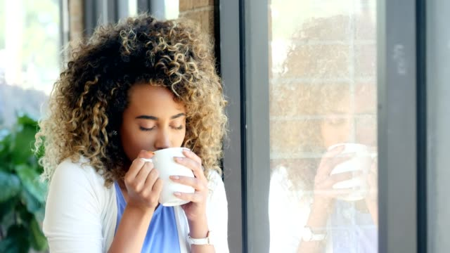 pretty young woman enjoys a hot cup of coffee in her home - curly hair stock videos & royalty-free footage