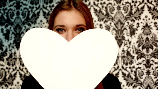 Hübsche Junge Frau Lachen mit peaper Herz in den Armen