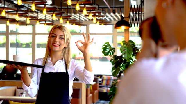 vídeos de stock e filmes b-roll de pretty young woman making ok sign with her left hand, while looking at camera. - empregada de mesa