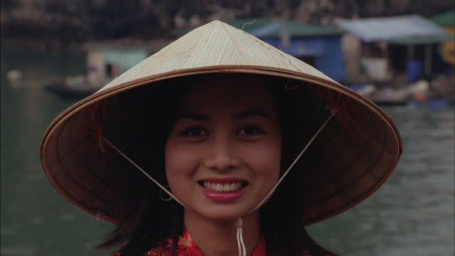a pretty young woman models a conical straw hat. - straw hat stock videos & royalty-free footage