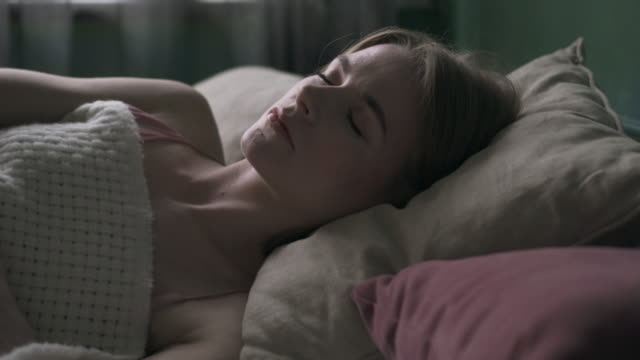 pretty young woman sleeping in bed under blanket - eyes closed stock videos and b-roll footage