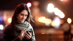 Pretty young woman smiling, using her smartphone at night. Lady in the street in cold weather. Modern technology