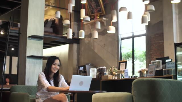 カフェでコンピューターを使ってかなり若い女性 - コミュニケーション点の映像素材/bロール