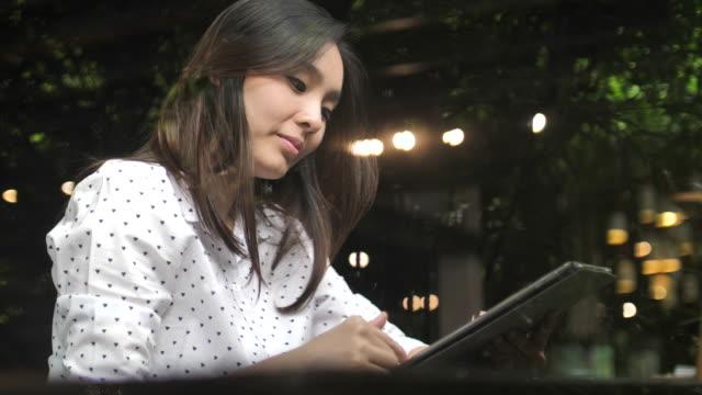 ganska ung kvinna med digital tablett i café, slow motion - människofinger bildbanksvideor och videomaterial från bakom kulisserna