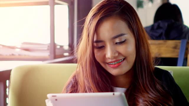 美しい若い女性のデジタルタブレットを使用して、カフェ - 指差す点の映像素材/bロール