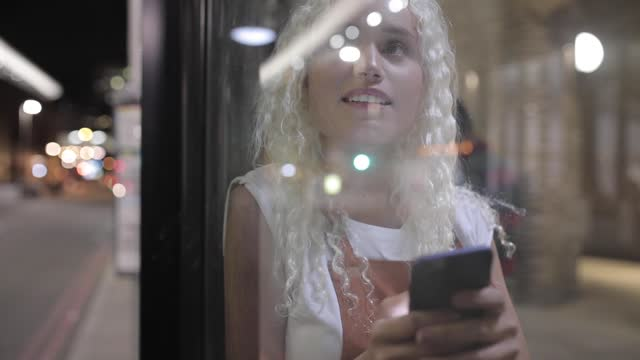 pretty young woman waiting at bus stop, typing message, london, uk - waiting stock videos & royalty-free footage