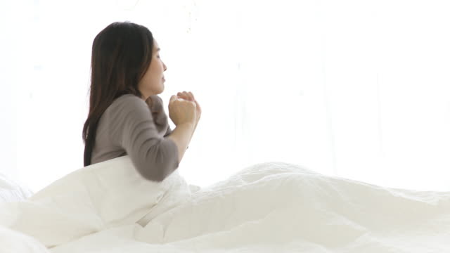 hübsche junge frau aufwachen in der früh auf weißen bett - only young women stock-videos und b-roll-filmmaterial