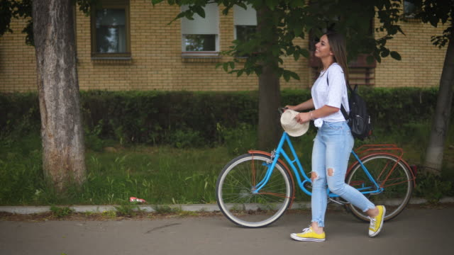 pretty young woman walking and pushing her bicycle. - young women stock videos & royalty-free footage