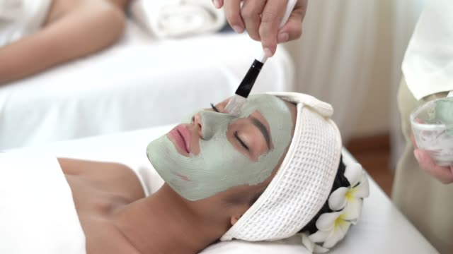 vídeos de stock e filmes b-roll de pretty young woman with facial mask - cuidado com o corpo