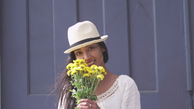 pretty young woman with yellow flowers poses for photographer. - bunch of flowers stock videos and b-roll footage