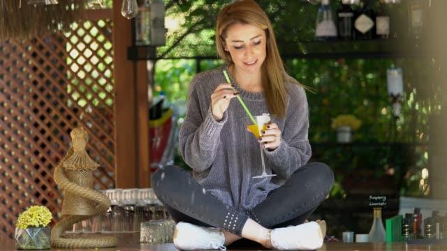 stockvideo's en b-roll-footage met mooie jonge vrouwen drinken een cocktail op toog - tropische drankjes