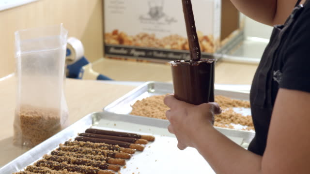 CU  pretzel stick dipped in hot chocolate then placed on baking tray and blanched almond mix sprinkled over chocolate covered pretzel sticks on baking tray / Rancho Mirage, California, USA