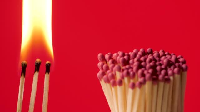 感染症の蔓延を防ぐ - パンデミックを破る - 燃えるマッチ棒、赤い背景 - マッチ箱点の映像素材/bロール