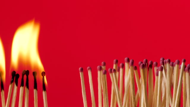 preventing the spread of infectious diseases - break pandemic - burning matchstick, red background, slow motion - epidemia video stock e b–roll
