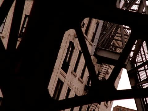 pre-war apartment building behind steel beams & steps of subway station building. shaking, hand held. - 非常階段点の映像素材/bロール