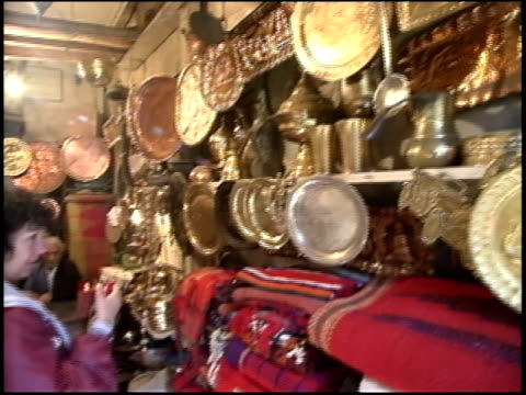 prewar iraq / ms pan american woman browsing in iraqi coppersmith's store / iraq - solo un uomo anziano video stock e b–roll