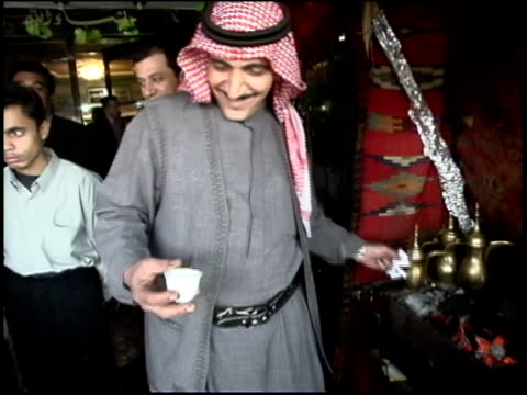 prewar iraq / ms iraqi man pan pouring espresso from gold pot and offering to camera / iraq / audio - 注ぎ口点の映像素材/bロール