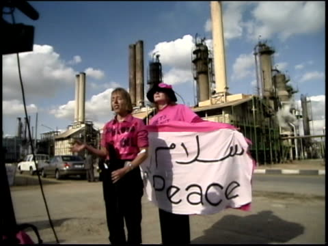 pre-war iraq / oil refinery / pink activists speaking to reporters, holding peace banners and posing in group / iraq / audio - western script stock videos & royalty-free footage