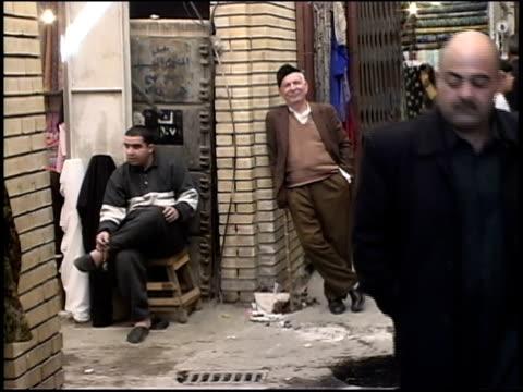 Prewar Iraq / WS MS Street market scenes / MS Man trying on keffiyeh / Iraq