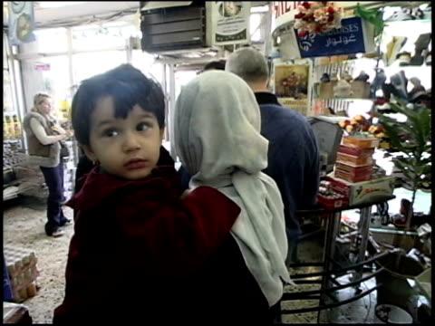 Prewar Iraq / WS Street scenes / MS Couple making purchase in store / Iraq