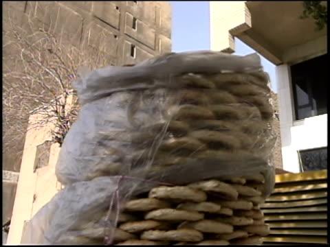 Prewar Iraq / WS Street scenes / MS Woman at sewing machine / MS Construction workers / Iraq / AUDIO