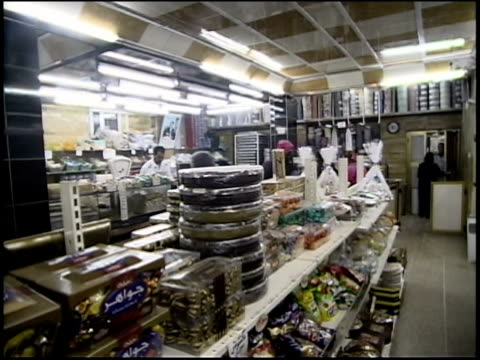 prewar iraq / ms ws cu tour group in iraqi bakery eating flour pastries / iraq / audio - butiksskylt bildbanksvideor och videomaterial från bakom kulisserna
