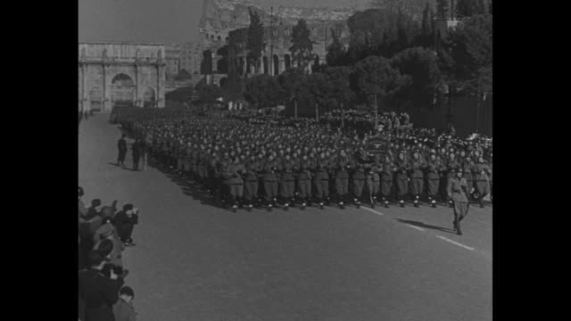 preworld war ii italy / italian soldiers stand at attention with arch of constantine in bg / benito mussolini walks with woman and large group of... - parade stock videos & royalty-free footage