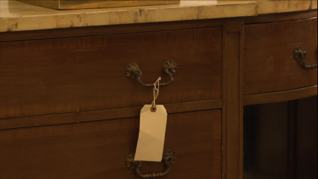 vídeos de stock, filmes e b-roll de price tags hang from merchandise in an antiques shop. - antiquário loja
