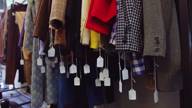 vídeos de stock e filmes b-roll de price tags swinging in second hand clothing store - fora de moda estilo