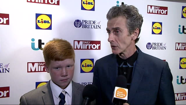 pride of britain awards 2014; peter capaldi interview sot - what a brave guy ext / night bruce forsyth on red carpet cheryl fernandez-versini on red... - フィリップ スコフィールド点の映像素材/bロール