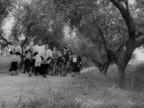 vidéos et rushes de priest and altar boys leads a congregation along a country lane. - prêtre
