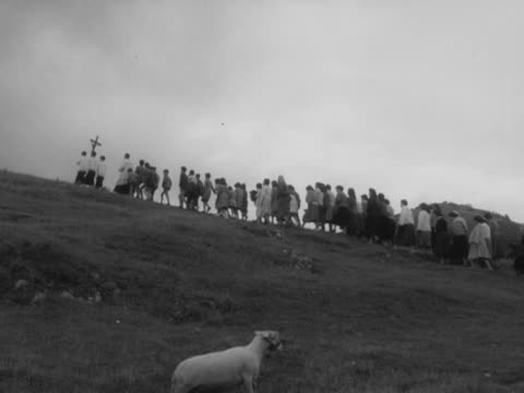 vidéos et rushes de priest and altar boys leads a congregation up a hillside. - prêtre