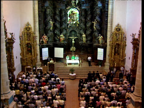 Priest and worshippers stand in Catholic church ready to begin Mass Basque Country Spain