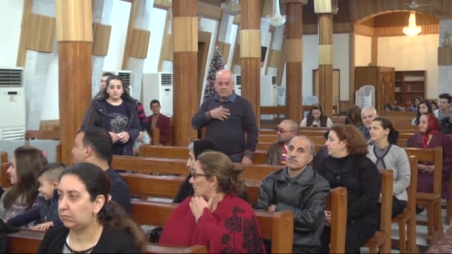 priest batris sito leads a christmas mass held to mark the birth of jesus christ at the seyyidet'ul necat church in baghdad, iraq on december 25,... - キリスト降誕点の映像素材/bロール